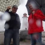 Otmar und ich im Regen vor einem der schoensten Leuchttuerme Kanadas im Fischerdorf Peggys Cove.