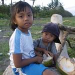 Kinder am Vulkanstrand von Bali beim Aushoehlen einer Kokusnuss